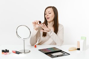 Beautiful young woman painting nails with red nail polish, sitting at table applying makeup with set facial decorative cosmetics isolated on white background. Beauty female fashion lifestyle concept.