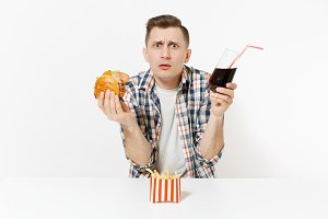 Handsome disgusted, abhorred man sitting at table with burger, french fries, cola in glass isolated on white background. Proper nutrition or American classic fast food. Advertising area, copy space.