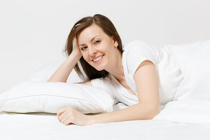 Calm young brunette woman lying in bed with white sheet, pillow, blanket on white background. Smiling beauty female spending time in room. Rest, relax, good mood concept. Copy space for advertisement.