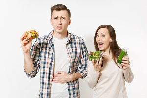 Couple painful man and woman standing with green detox smoothies, salad in glass bowl, burger isolated on white background. Proper nutrition, healthy lifestyle, fast food, choice concept. Copy space.