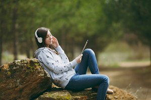 Young relaxing woman in casual clothes sitting on stone listening music with headphones and tablet pc computer in city park or forest on green blurred background. Student lifestyle, leisure concept.