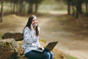Young smiling business woman or student in casual clothes sitting on stone talking on mobile phone in city park or forest using laptop working outdoors on green background. Mobile Office concept.