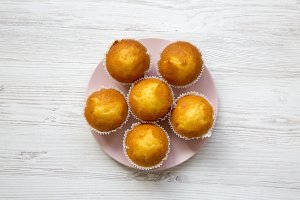 Tasty muffins on pink plate over