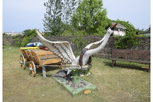 A statue of a swan harnessed to a cart.