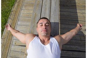 man is lying on a bench and stretching. A smile on the face of a man lying on a bench.