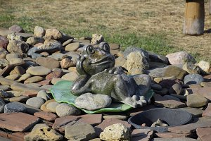 Statue of a frog on a water lily. A statue on pebbles.