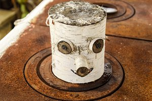 Toy souvenir from a birch log. eyes nose and mouth are made on a birch log.