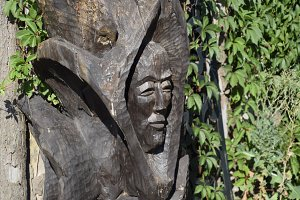 Wooden idol. Woodcarving. Man's face is carved on the trunk of a log.