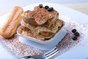 Piece of appetizing homemade tiramisu cake on plate in close up.