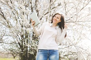 Young happy beautiful woman in casual clothes with headphones holding tablet pc computer pointing index finger up in city garden or park on blooming tree background. Spring flowers. Lifestyle concept.