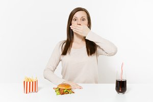Woman cover mouth with hand at table with burger, french fries, cola in glass bottle isolated on white background. Proper nutrition or American classic fast food. Advertising area with copy space.