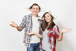 Young smiling woman, man in casual clothes and newspaper hats spreading hands. Happy couple isolated on white background. Instruments, accessories for renovation apartment room. Repair home concept.