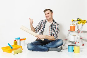 Man pointing finger aside on copy space, sits on floor with roll of wallpaper, instruments for renovation apartment isolated on white background. Gluing accessories, painting tools. Repair concept.