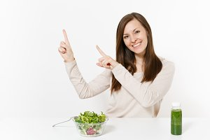 Young woman at table with green detox smoothies, salad in glass bowl pointing fingers on copy space isolated on white background. Proper nutrition, vegetarian food, healthy lifestyle, dieting concept.