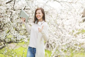 Young smiling beautiful woman in light casual clothes with headphones holding tablet pc computer showing thumb up in city garden or park on blooming tree background. Spring flowers. Lifestyle concept.