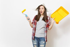 Young shocked beautiful woman in newspaper hat holding roller for wall painting and paint tray isolated on white background. Instruments, tools for renovation apartment room. Repair home concept.