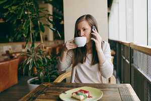 Young woman sitting alone in coffee shop at table with cup of cappuccino, cake, relaxing in restaurant during free time. Young female talking on mobile phone, having rest in cafe. Lifestyle concept.