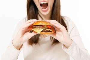 Close up cropped shot young woman holding in hands burger, trying to eat isolated on white background. Proper nutrition or American classic fast food. Copy space for advertisement. Advertising area.