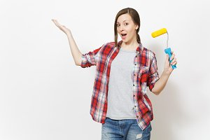 Young concerned woman holding paint roller for wall painting and pointing hand aside on copy space isolated on white background. Instruments for renovation apartment room. Repair home concept.