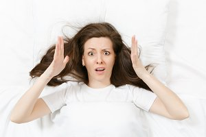 Top view of head of tired brunette young woman lying in bed with white sheet, pillow, blanket. Shocked female cover ears with hand, spending time in room. Rest, relax, good mood concept. Copy space.
