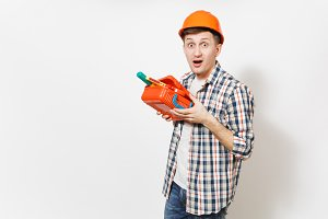 Young shocked handsome man in protective orange hardhat holding case with instruments or toolbox isolated on white background. Instruments, tools for renovation apartment room. Repair home concept.