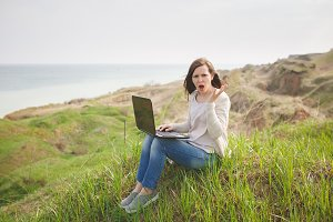 Young irritated dissatisfied business woman or student in casual clothes sitting on grass using laptop in field spreading hands working outdoors on green background. Mobile Office. Lifestyle concept.