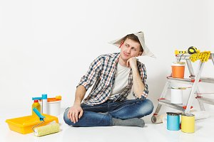 Male in newspaper hat with pencil behind ear sitting on floor with instruments for renovation apartment isolated on white background. Wallpaper, gluing accessories, painting tools. Repair concept.
