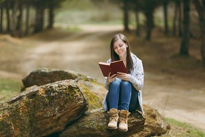 Young smiling beautiful woman in casual clothes sitting on stone studying reading book in big city park or forest on green blurred background. Student learning, education. Lifestyle, leisure concept.