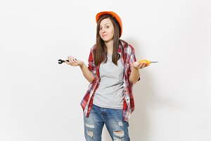 Young dissatisfied woman in protective construction orange helmet holding toy screwdriver and wrench isolated on white background. Instruments for renovation apartment room. Repair home concept.