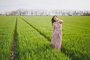 Young brunette smiling relaxed beautiful woman in light patterned dress keeping hand near neck walking in sunny weather in field on green background. Beautiful landscape. Lifestyle, leisure concept.
