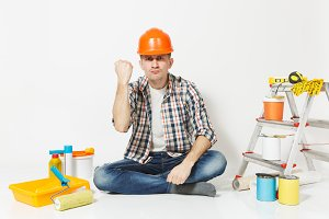 Serious man in orange protective helmet sitting on floor with instruments for renovation apartment room isolated on white background. Wallpaper gluing accessories, painting tools. Repair home concept.
