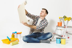 Handsome man sitting on floor with unfolded roll of wallpaper instruments for renovation apartment room isolated on white background. Gluing accessories painting tools. Repair home concept. Copy space