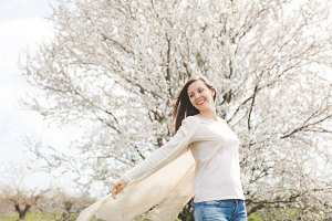 Young happy relaxed smiling beautiful woman in light casual clothes spreading hands standing in city garden or park on blooming tree background. Spring nature, flowers. Lifestyle, leisure concept.