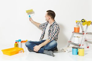 Man sitting on floor using on wall paint roller, instruments for renovation apartment room isolated on white background. Wallpaper, gluing accessories, painting tools. Repair home concept. Copy space.