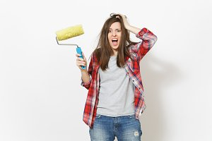 Young crazy loony woman in casual clothes holding paint roller for wall painting and clinging to head isolated on white background. Instruments for renovation apartment room. Repair home concept.