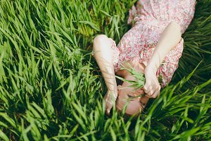 Young charming woman in light patterned dress lying on grass keeping hands near face looking up resting in sunny weather in field on bright green background. Spring nature. Lifestyle, leisure concept.