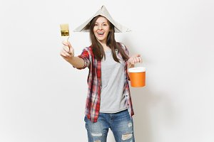 Young overjoyed beautiful woman in newspaper hat holding paint bucket and showing paint brush on camera isolated on white background. Instruments for renovation apartment room. Repair home concept.