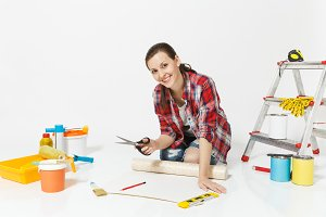 Woman sitting with wallpaper rolls, big scissors, pencil, instruments for renovation apartment isolated on white background. Accessories for gluing, painting tools. Repair home concept. Copy space.