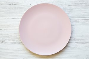 Empty pink plate on white wooden