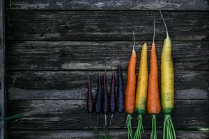 Colored organic carrots over rustic wooden background closeup. Top view
