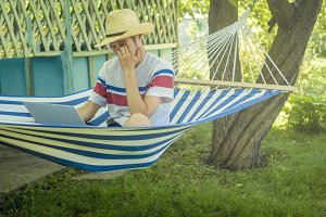young freelancer sitting in hammock working on travel vacation