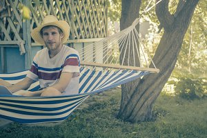 young man sitting in hammock working with laptop vintage toned