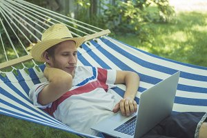 young male freelancer working lying on striped hammock in garden on summer day