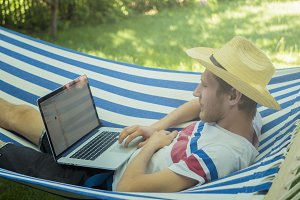 back view of young male programmer in hat typing on his laptop in hammock