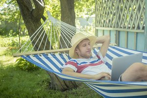 young relaxing man in summer hat in hammock with opened laptop in the yard
