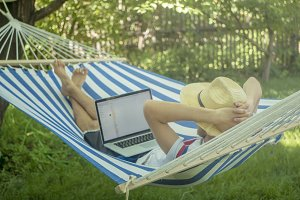 back view of lying young man in hat working with laptop on hammock on a summer day
