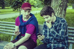 two young guys smiling scrolling the news on phones and checking photo