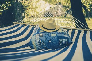close up empty hammock with blue and white stripes on a simmer day in tropical forest
