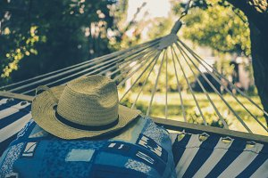 close up summer women hat on a pillow on hammock on a sunny summer day