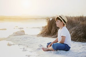 pensive boy sitting on the beach
